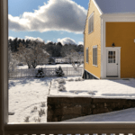 Photograph of yellow barn in snow